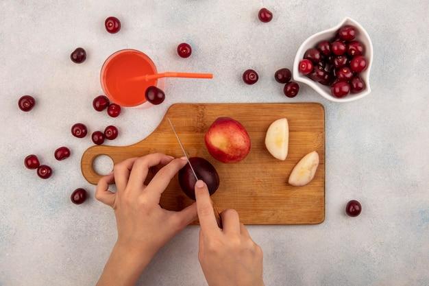 Vista superior das mãos femininas cortando pêssego com faca na tábua e suco de cereja com tigela de cereja no fundo branco Foto gratuita