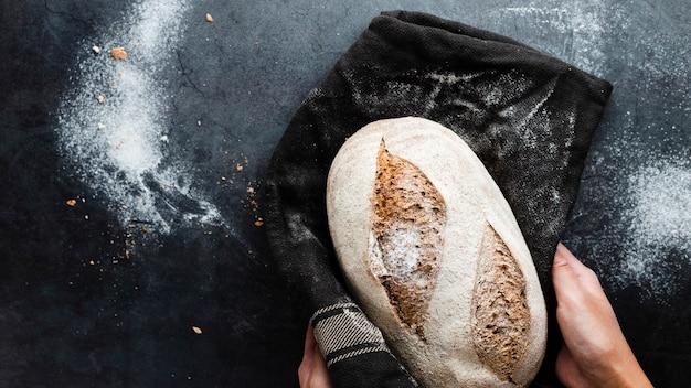 Vista superior das mãos segurando um pão no pano Foto gratuita