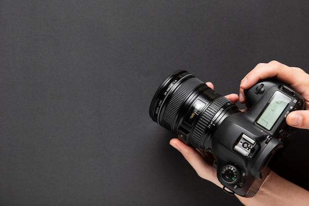 Vista superior das mãos segurando uma câmera com espaço de cópia Foto gratuita