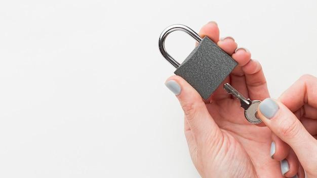 Vista superior das mãos segurando uma fechadura e chave com espaço de cópia Foto gratuita