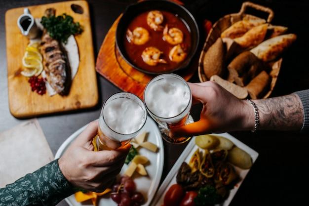 Vista superior das mãos segurando uma superfície de pub de copos de cerveja Foto gratuita