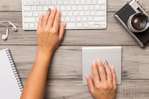 Vista superior das mãos trabalhando no computador na área de trabalho com câmera fotográfica Foto gratuita