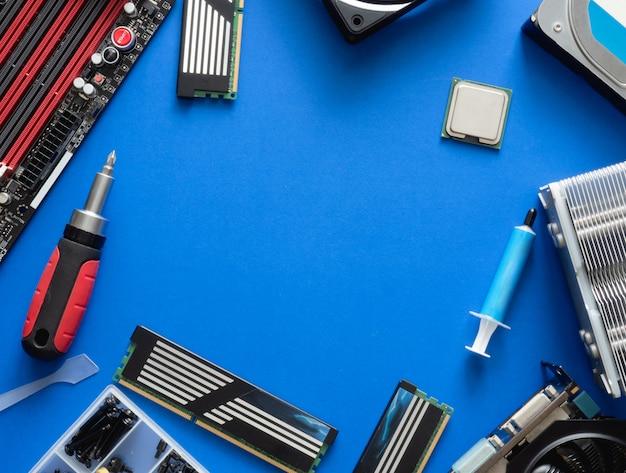 Vista superior das peças do computador com disco rígido, memória ram, cpu, placa gráfica e placa-mãe no fundo da tabela azul. Foto Premium