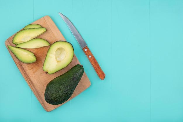 Vista superior de abacate fresco fatiado com faca na placa de madeira da cozinha em azul Foto gratuita