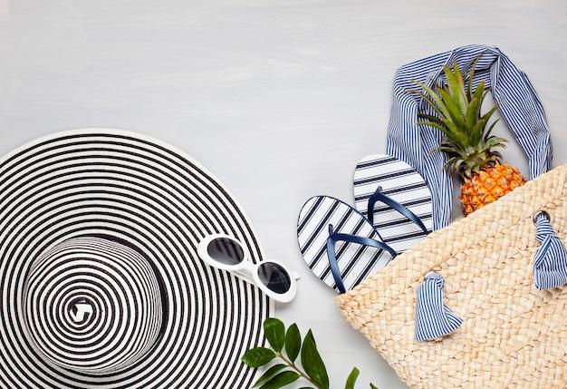 Vista superior de acessórios de praia tropical com chapéu e flip-flops Foto Premium