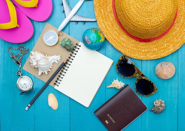 Vista superior de acessórios de viagem na luz azul piso de tábua de madeira para o tempo de férias de verão Foto Premium
