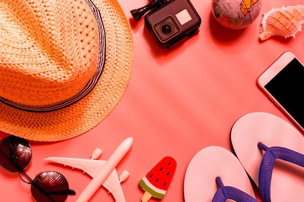 Vista superior de acessórios do viajante, folha de palmeira tropical e avião no fundo cor-de-rosa. Foto Premium