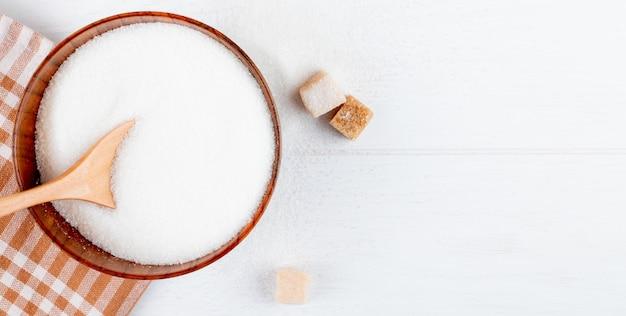 Vista superior de açúcar branco em uma tigela de madeira com uma colher e cubos de açúcar em fundo branco, com espaço de cópia Foto gratuita