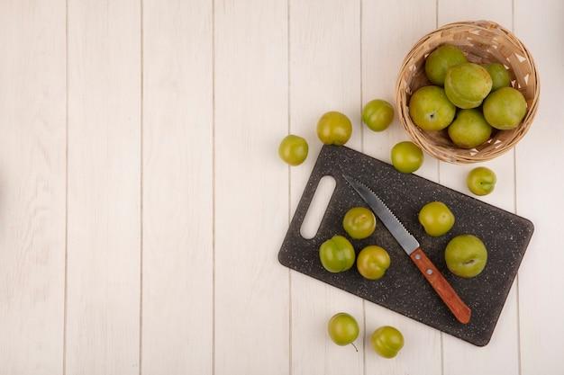 Vista superior de ameixas de cereja verdes frescas em uma tábua de cozinha com faca com ameixas de cereja em um balde em um fundo branco de madeira com espaço de cópia Foto gratuita