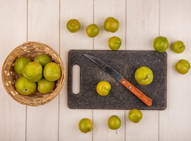 Vista superior de ameixas de cereja verdes frescas em uma tábua de cozinha com uma faca com ameixas de cereja em um balde em um fundo branco de madeira Foto gratuita