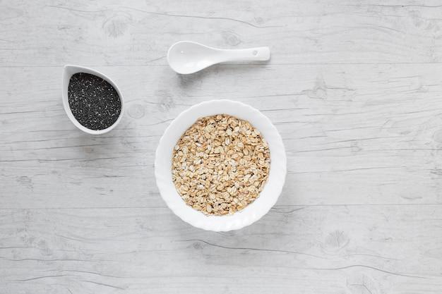 Vista superior de aveia; sementes de chia e colher contra a mesa de madeira Foto gratuita