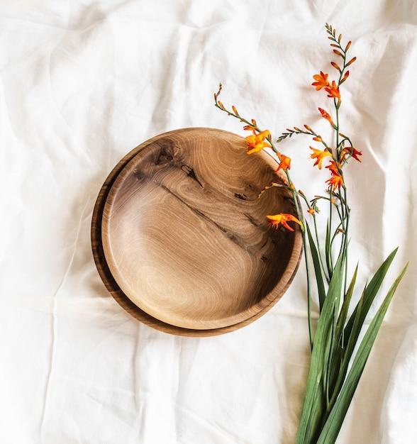 Vista superior de bacias de madeira artesanais redondas vazias marrons e flores de laranja na toalha de mesa de algodão branco. postura plana. cópia sapce Foto Premium