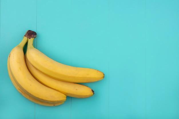 Vista superior de bananas em uma superfície turquesa Foto gratuita