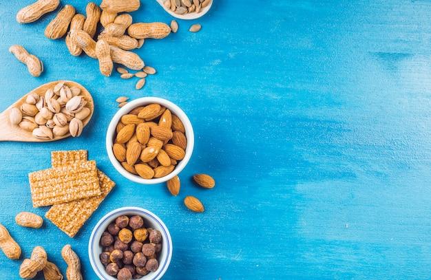 Vista superior, de, barra saudável, feito, com, frutas secadas, e, sementes, ligado, azul, pintado, fundo Foto gratuita