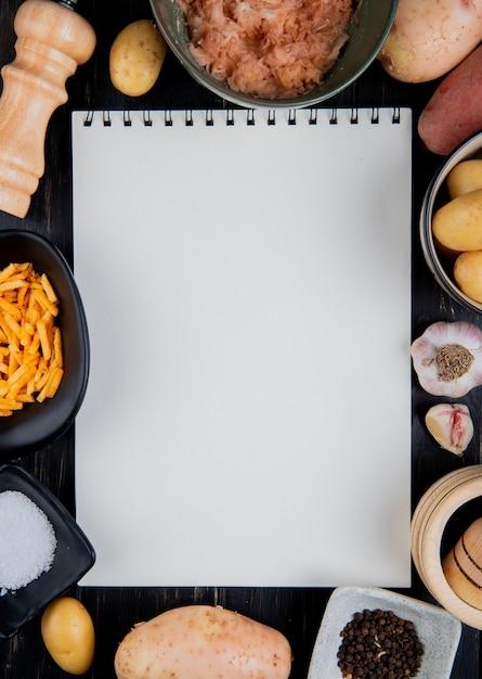 Vista superior de batatas fatiadas e inteiras raladas em torno do bloco de notas com sal pimenta preta na superfície de madeira com espaço de cópia Foto gratuita