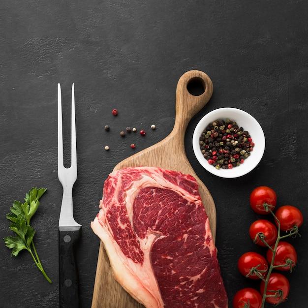 Vista superior de bife fresco na mesa com tomate cereja Foto gratuita