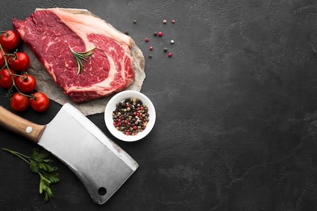 Vista superior de bife fresco na mesa com tomates Foto gratuita