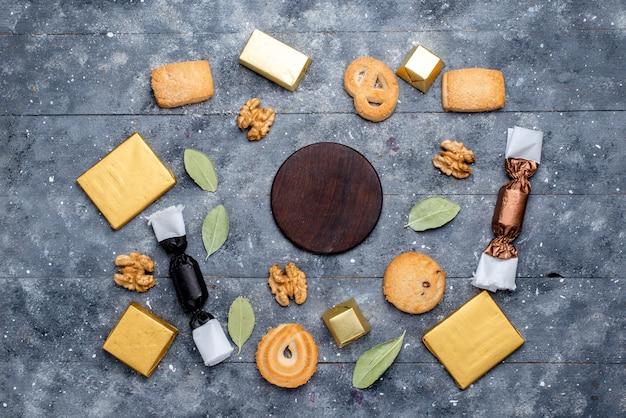 Vista superior de biscoito e nozes junto com bolo de chocolate na mesa cinza, biscoito biscoito com açúcar doce de chocolate Foto gratuita