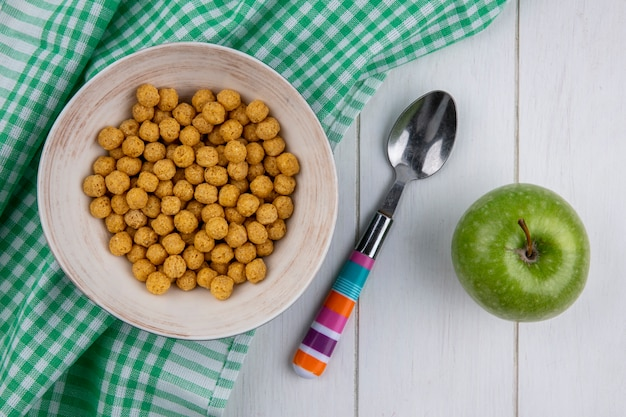 Vista superior de bolas de milho em uma toalha xadrez com uma colher colorida e uma maçã verde em uma superfície branca Foto gratuita
