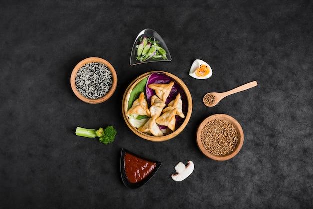 Vista superior de bolinhos de massa em vapor cercada com gergelim; molho; sementes de coentro; brócolis e cogumelo em fundo preto Foto gratuita