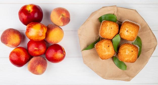 Vista superior de bolos com folhas verdes em papel ofício marrom com nectarinas maduras frescas em madeira rústica branca Foto gratuita