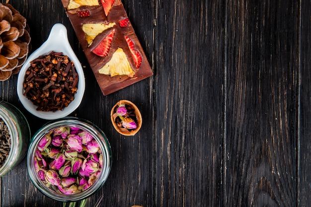Vista superior de botões de rosa em uma jarra de vidro, especiarias cravo e barra de chocolate com frutas em madeira preta, com espaço de cópia Foto gratuita
