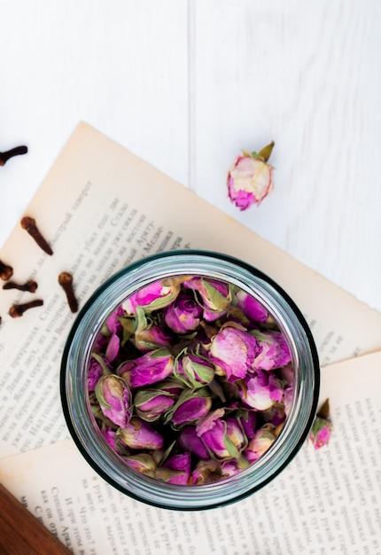 Vista superior de botões de rosa seco de chá em uma jarra de vidro nas páginas do livro Foto gratuita