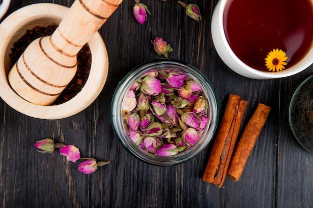 Vista superior de botões de rosa secos em frasco de vidro com paus de canela e argamassa de madeira cheia de pimenta preta e uma xícara de chá em madeira preta Foto gratuita