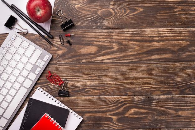 Vista superior de cadernos e maçã na mesa de madeira com espaço de cópia Foto gratuita