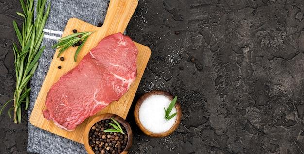 Vista superior de carne com especiarias e ervas aromáticas Foto gratuita