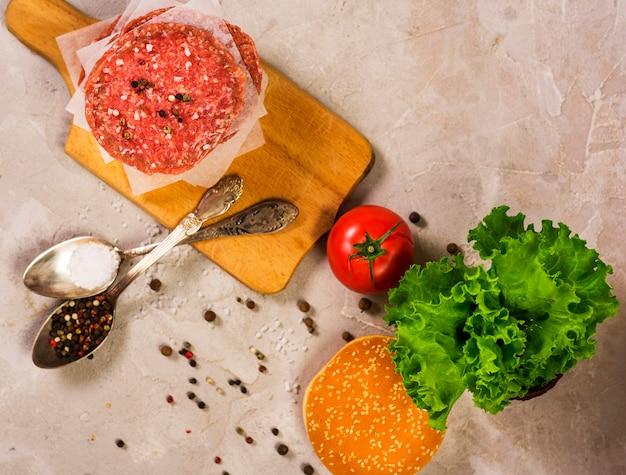 Vista superior de carne crua hambúrguer em uma mesa de madeira Foto gratuita