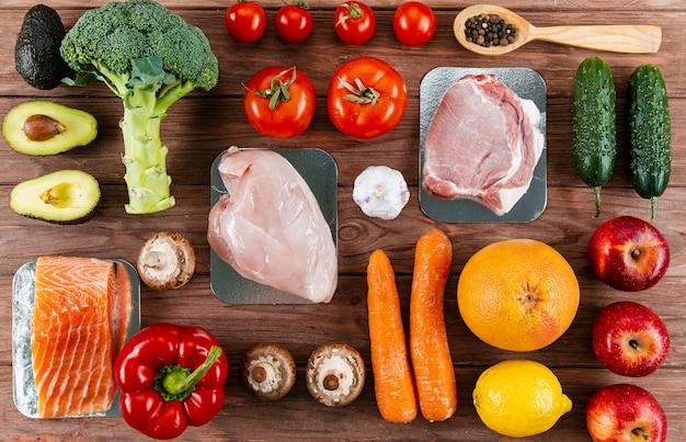 Vista superior de carnes organizadas com legumes Foto Premium