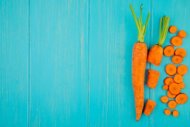 Vista superior de cenouras cortadas inteiras cortadas no lado direito e fundo azul com espaço de cópia Foto gratuita
