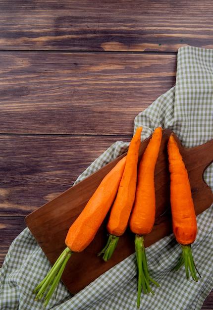 Vista superior de cenouras na tábua no pano e fundo de madeira com espaço de cópia Foto gratuita