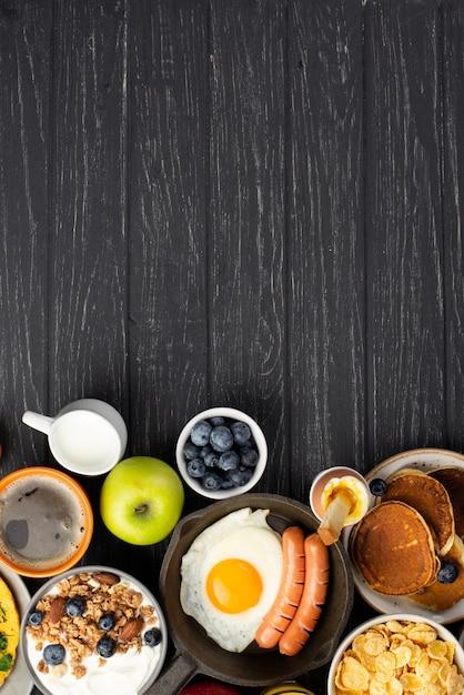 Vista superior de cereais e iogurte com salsichas e ovo no café da manhã Foto gratuita