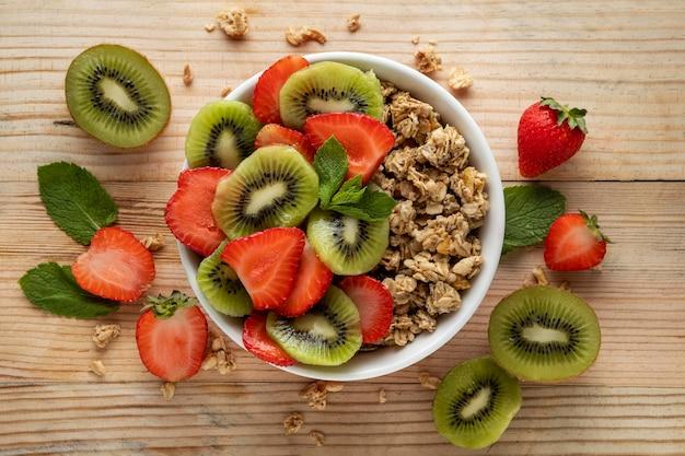 Vista superior de cereais matinais em uma tigela com frutas Foto gratuita