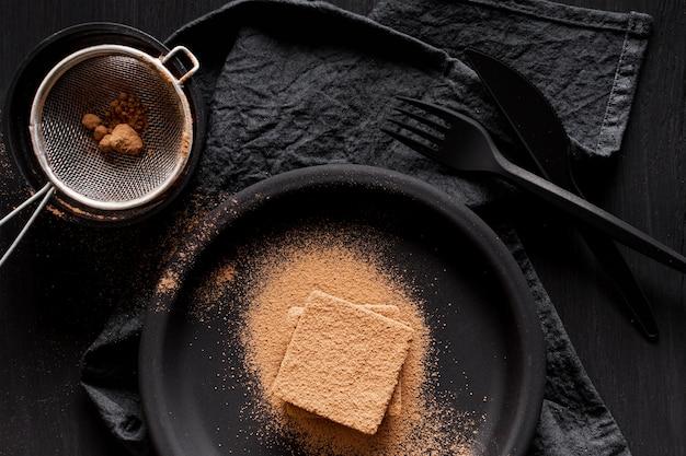 Vista superior de chocolate em pó e peneira Foto gratuita
