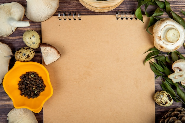 Vista superior de cogumelos frescos ovos de codorna pimenta preta, dispostos em torno de um caderno de desenho em madeira rústica Foto gratuita