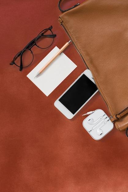 Vista superior de coisas de viajante hipster de mulher com telefone, bloco de notas, óculos e fone de ouvido Foto Premium