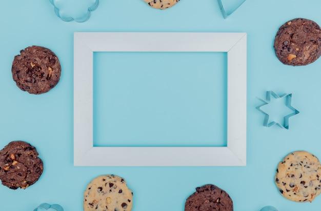 Vista superior de cookies em torno do quadro sobre fundo azul, com espaço de cópia Foto gratuita
