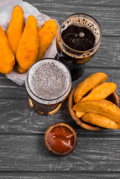 Vista superior de copos de cerveja e batatas fritas Foto gratuita