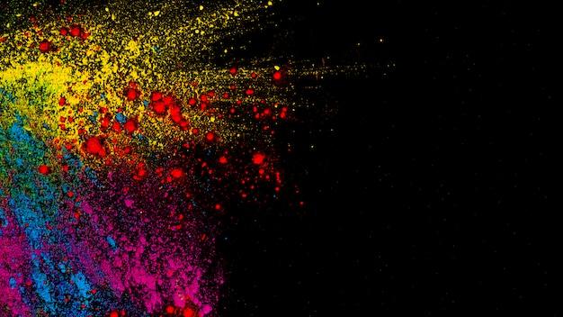 Vista superior de cores coloridas holi na frente do pano de fundo preto Foto gratuita