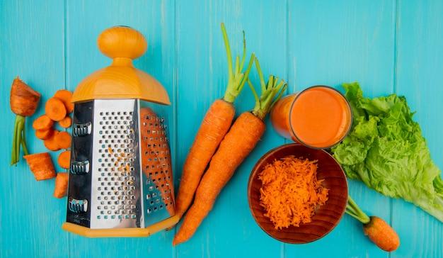 Vista superior de corte todo ralado cenouras fatiadas com ralador de metal alface e suco de cenoura na mesa azul Foto gratuita