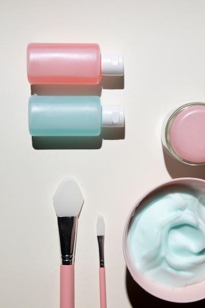 Vista superior de cosméticos corpo com fundo liso Foto gratuita