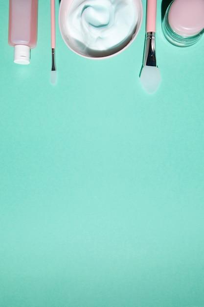 Vista superior de cosméticos no fundo liso Foto gratuita