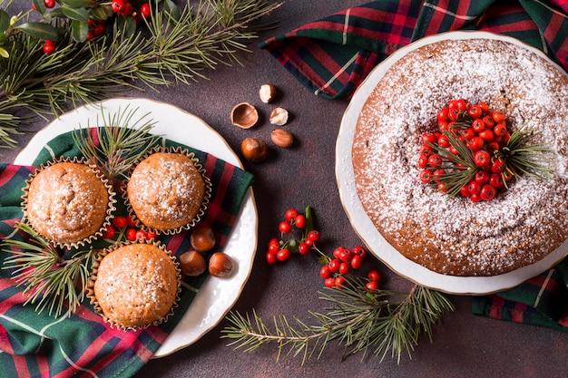 Vista superior de cupcakes e bolo de natal com frutas vermelhas Foto gratuita