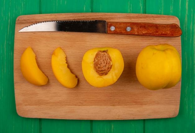 Vista superior de damascos inteiros cortados e fatiados com uma faca na tábua sobre fundo verde Foto gratuita