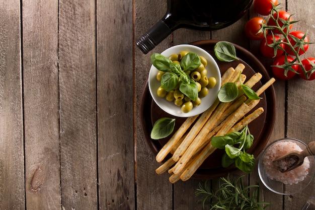 Vista superior de deliciosas azeitonas com outros produtos na superfície de madeira Foto gratuita