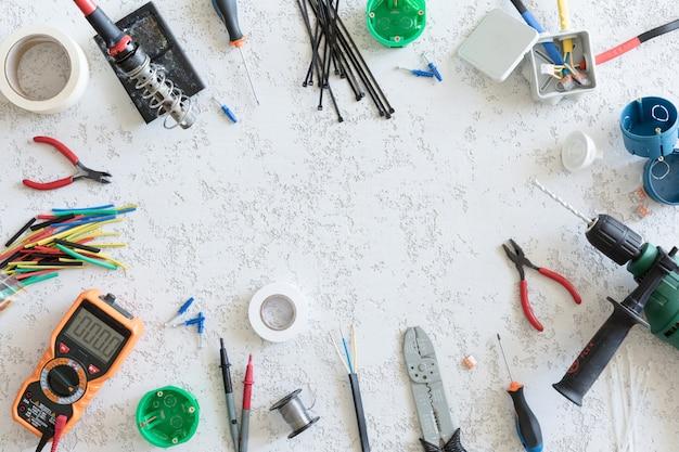 Vista superior de diferentes ferramentas elétricas em fundo branco de concreto, configuração plana. ferramentas para eletricista, tensões e medições de corrente Foto Premium
