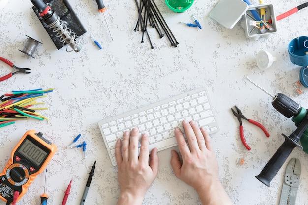 Vista superior de diferentes ferramentas elétricas, mão de homem no teclado do computador, plana leigos. ferramentas para eletricista, tensões e medições de corrente Foto Premium